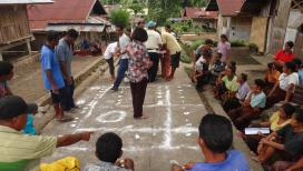 Community drawing a map on the ground as part of CLTS
