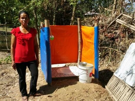 Mrs. Chea Sokhom standing in front of the hygienic latrine that her family built under the pilot of the phased-in budget support from the government of Cambodia